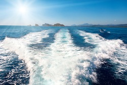 Waves on blue sea behind the speed boat water with bright sun shining on the sky