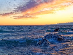 Waves on rocks during sunset, hazy water and waves on a colorful sunset