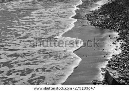 Waves on stone beach waters edge abstract sea background. Black and white.