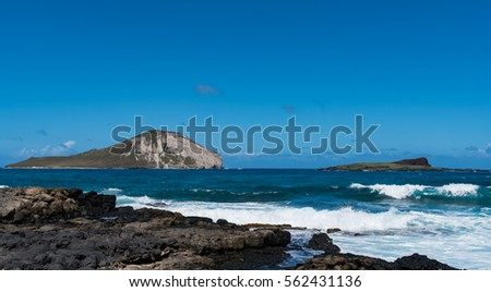 Waves rolling into the shore of Oahu with Rabbit Island and Kaohikaipu Island State Seabird Sanctuary #562431136