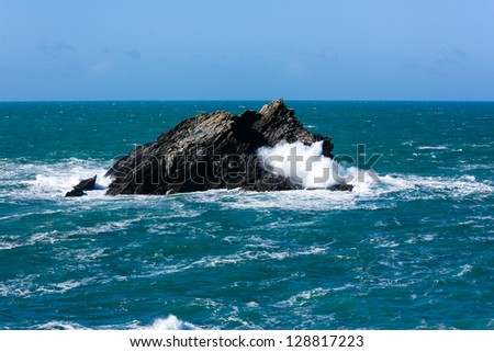 Waves smash into an offshore rock