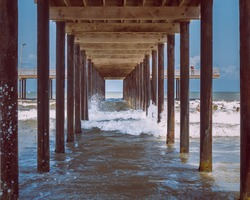 waves under the wooden pier on a clear day