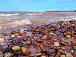 Waves wash up brightly colored rocks along the shoreline of Lake Superior at Porcupine Mountains Wilderness State Park Michigan