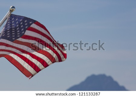 Waving American flag against cloudy blurred sky in the background.