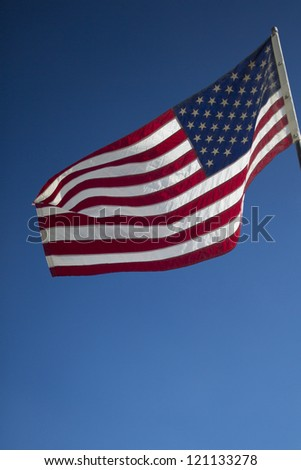 Waving American flag against cloudy sky
