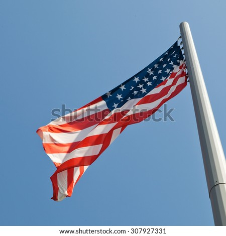 waving american flag over the blue sky