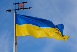 Waving blue-yellow Ukrainian flag with the emblem of Lviv at the height of the flagpole on the blue sky background. A horizontal view.