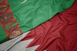 waving colorful flag of bahrain and national flag of turkmenistan. macro