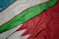 waving colorful flag of bahrain and national flag of uzbekistan. macro
