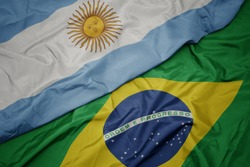 waving colorful flag of brazil and national flag of argentina. macro
