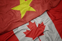 waving colorful flag of canada and national flag of vietnam. macro