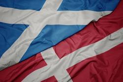 waving colorful flag of denmark and national flag of scotland. macro