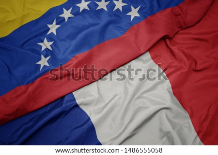 waving colorful flag of france and national flag of venezuela. macro #1486555058