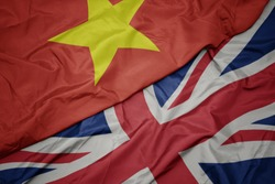 waving colorful flag of great britain and national flag of vietnam. macro