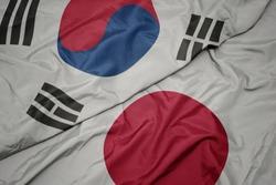 waving colorful flag of japan and national flag of south korea. macro