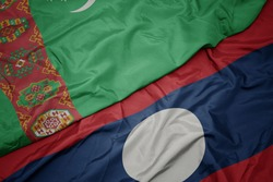 waving colorful flag of laos and national flag of turkmenistan. macro