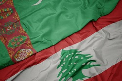 waving colorful flag of lebanon and national flag of turkmenistan. macro