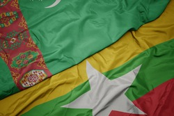waving colorful flag of myanmar and national flag of turkmenistan. macro