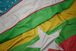 waving colorful flag of myanmar and national flag of uzbekistan. macro