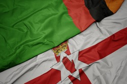 waving colorful flag of northern ireland and national flag of zambia. macro