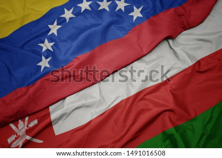 waving colorful flag of oman and national flag of venezuela. macro #1491016508