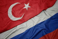 waving colorful flag of russia and national flag of turkey. macro