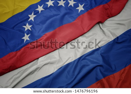 waving colorful flag of russia and national flag of venezuela. macro #1476796196
