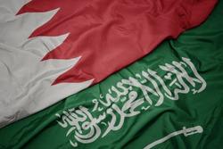 waving colorful flag of saudi arabia and national flag of bahrain. macro