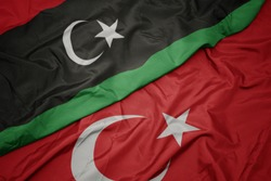 waving colorful flag of turkey and national flag of libya. macro