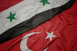 waving colorful flag of turkey and national flag of syria. macro
