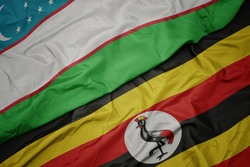 waving colorful flag of uganda and national flag of uzbekistan. macro