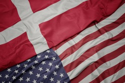 waving colorful flag of united states of america and national flag of denmark. macro
