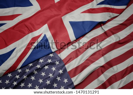 waving colorful flag of united states of america and national flag of great britain.