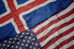 waving colorful flag of united states of america and national flag of iceland.