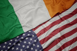 waving colorful flag of united states of america and national flag of ireland.