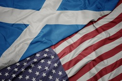 waving colorful flag of united states of america and national flag of scotland.