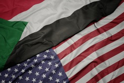 waving colorful flag of united states of america and national flag of sudan.