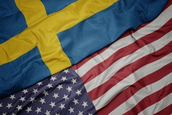 waving colorful flag of united states of america and national flag of sweden.