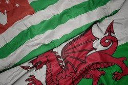 waving colorful flag of wales and national flag of abkhazia. macro
