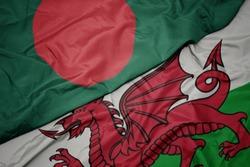 waving colorful flag of wales and national flag of bangladesh. macro