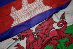 waving colorful flag of wales and national flag of cambodia. macro
