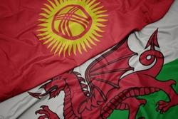 waving colorful flag of wales and national flag of kyrgyzstan. macro