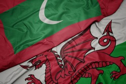 waving colorful flag of wales and national flag of maldives. macro