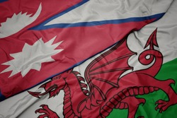 waving colorful flag of wales and national flag of nepal. macro