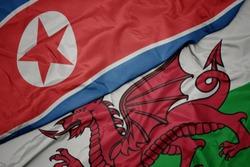 waving colorful flag of wales and national flag of north korea. macro
