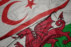 waving colorful flag of wales and national flag of northern cyprus. macro