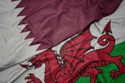 waving colorful flag of wales and national flag of qatar. macro