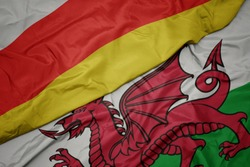 waving colorful flag of wales and national flag of south ossetia. macro