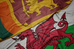 waving colorful flag of wales and national flag of sri lanka. macro