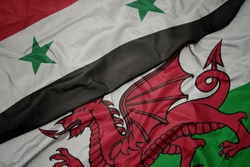 waving colorful flag of wales and national flag of syria. macro